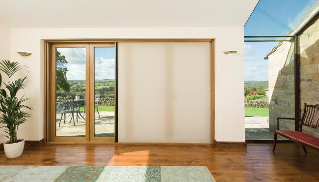 Centor oak bifold doors featuring a light-filtering shade for privacy and sun control