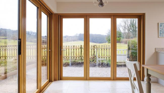 Two joining 205 Integrated Folding Doors with aligning panels overlooking farmland