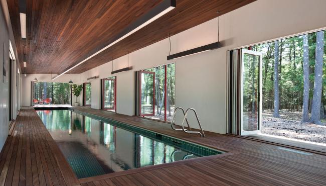 Centor integrated doors surrounding an indoor lap pool to allow a seamless connection to the forest outside